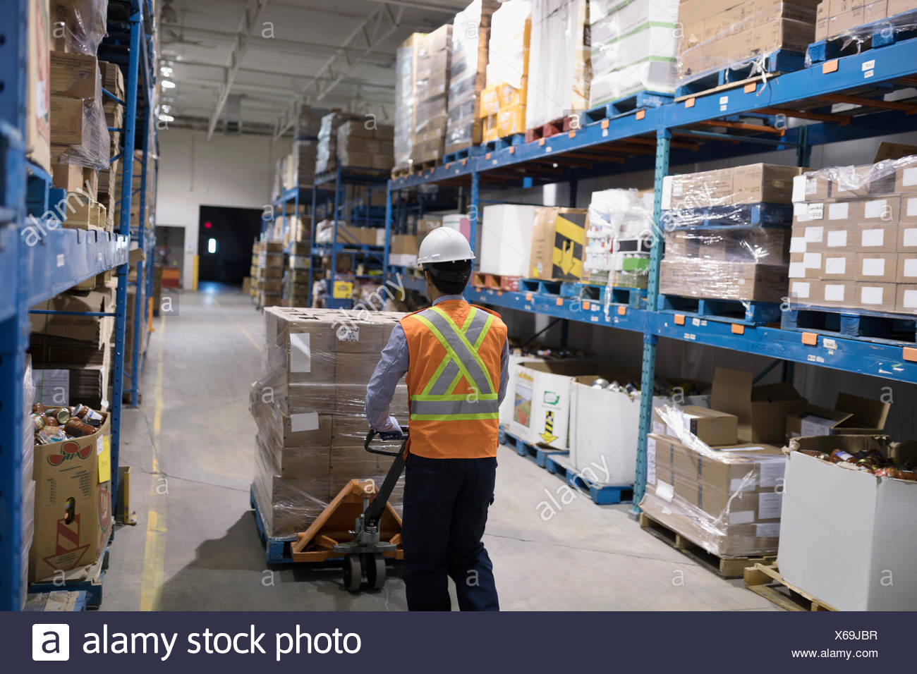 Worker pushing pallet jack with cardboard boxes in distribution warehouse - Stock Image