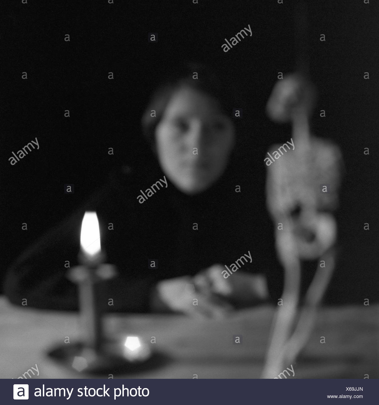 Sits woman table candle burns skeleton views fuzziness s/w people young expression seriously silence silence meditation Stock Photo