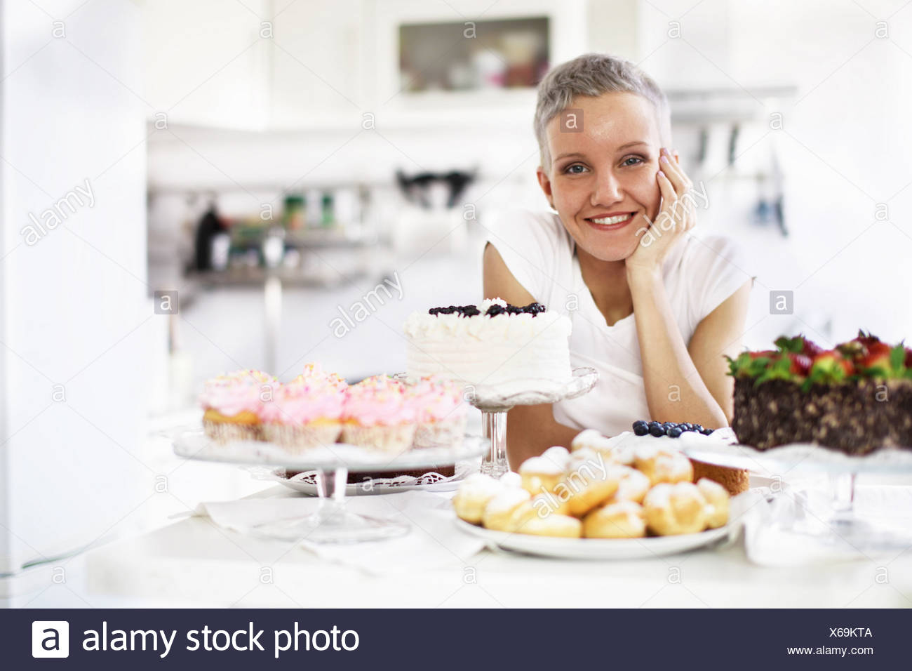 Portrait of woman with selection of hand made cakes - Stock Image