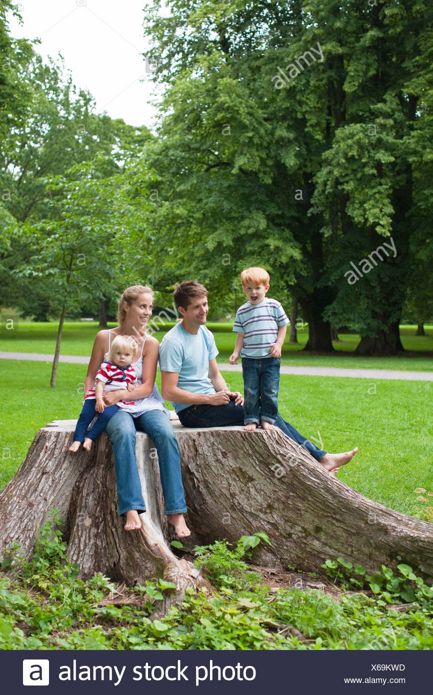 Mid adult couple with children sitting on stub in park and smiling - Stock Image