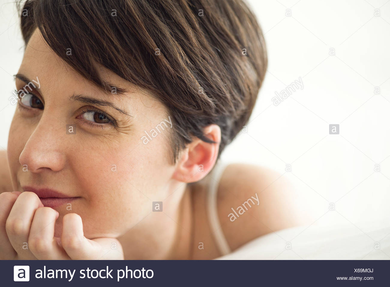Woman relaxing on bed, portrait - Stock Image