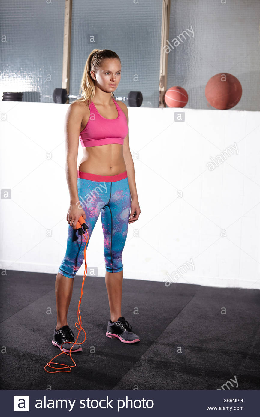 Portrait of young woman with skipping rope in gym - Stock Image
