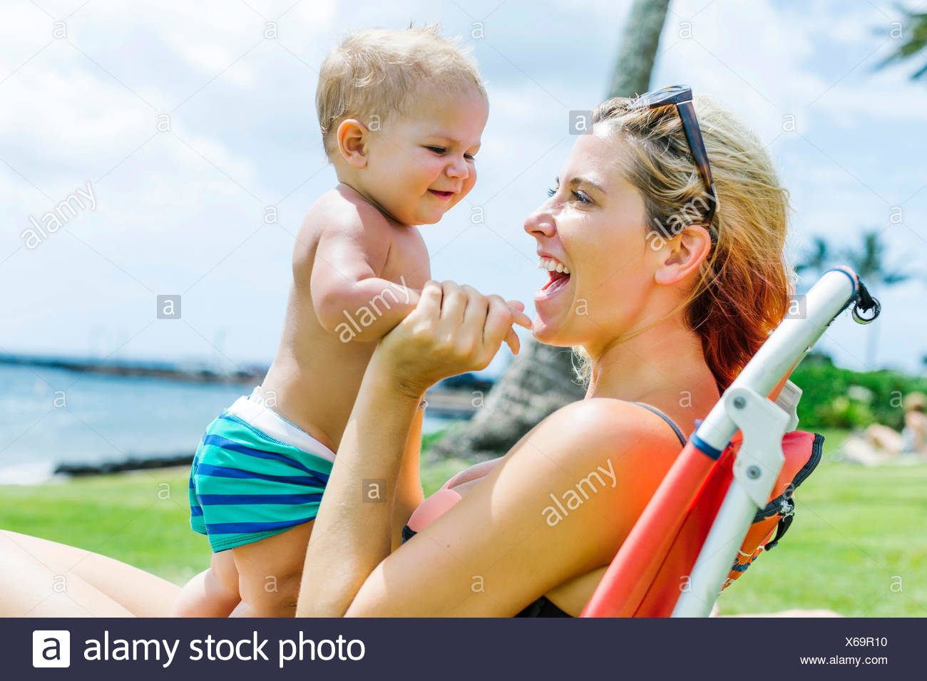 Woman sitting under palm tree with little son (18-23 months) - Stock Image