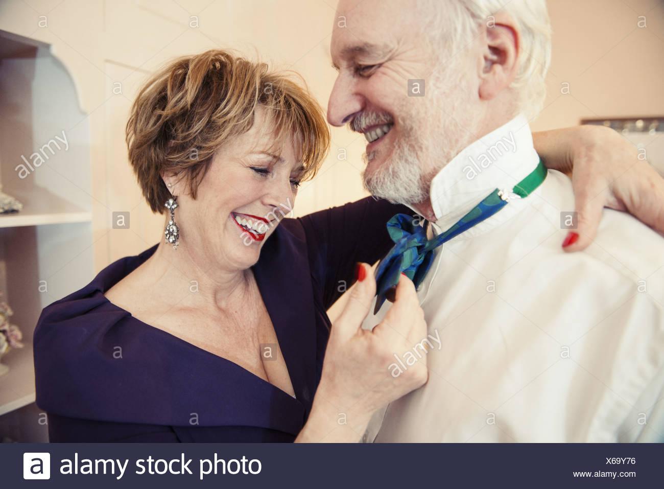 Mature woman putting bow tie on senior man - Stock Image