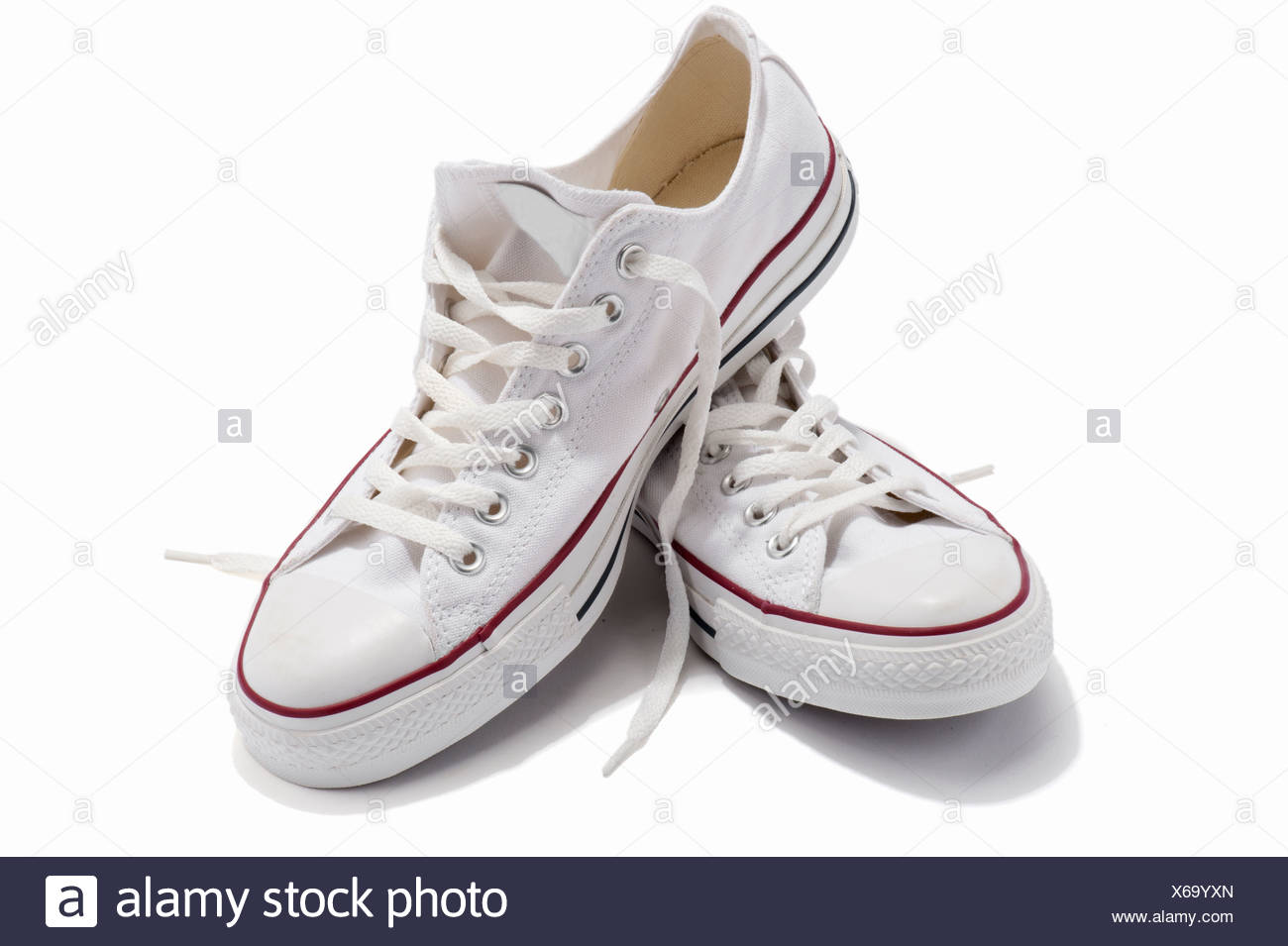 A pair of white lace up plimsolls - Stock Image