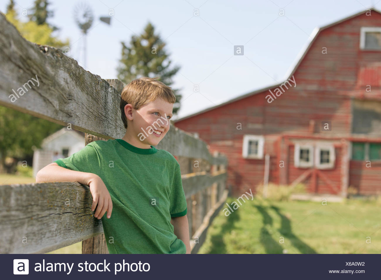 Young boy leaning on fence on rural property. Stock Photo