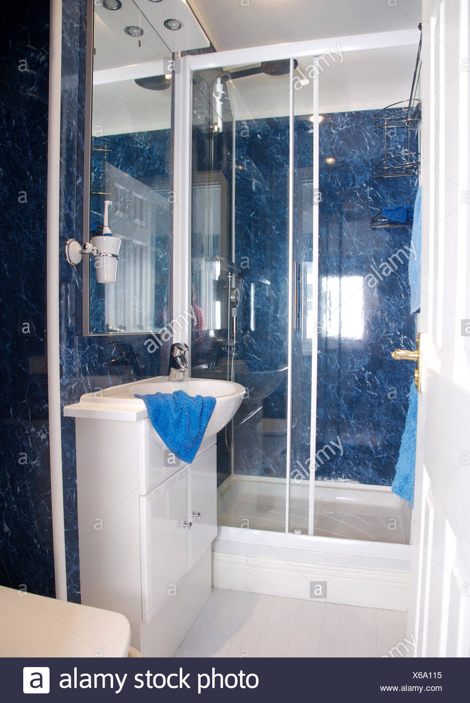 Vanity unit with fitted basin in small coastal bathroom with glass ...