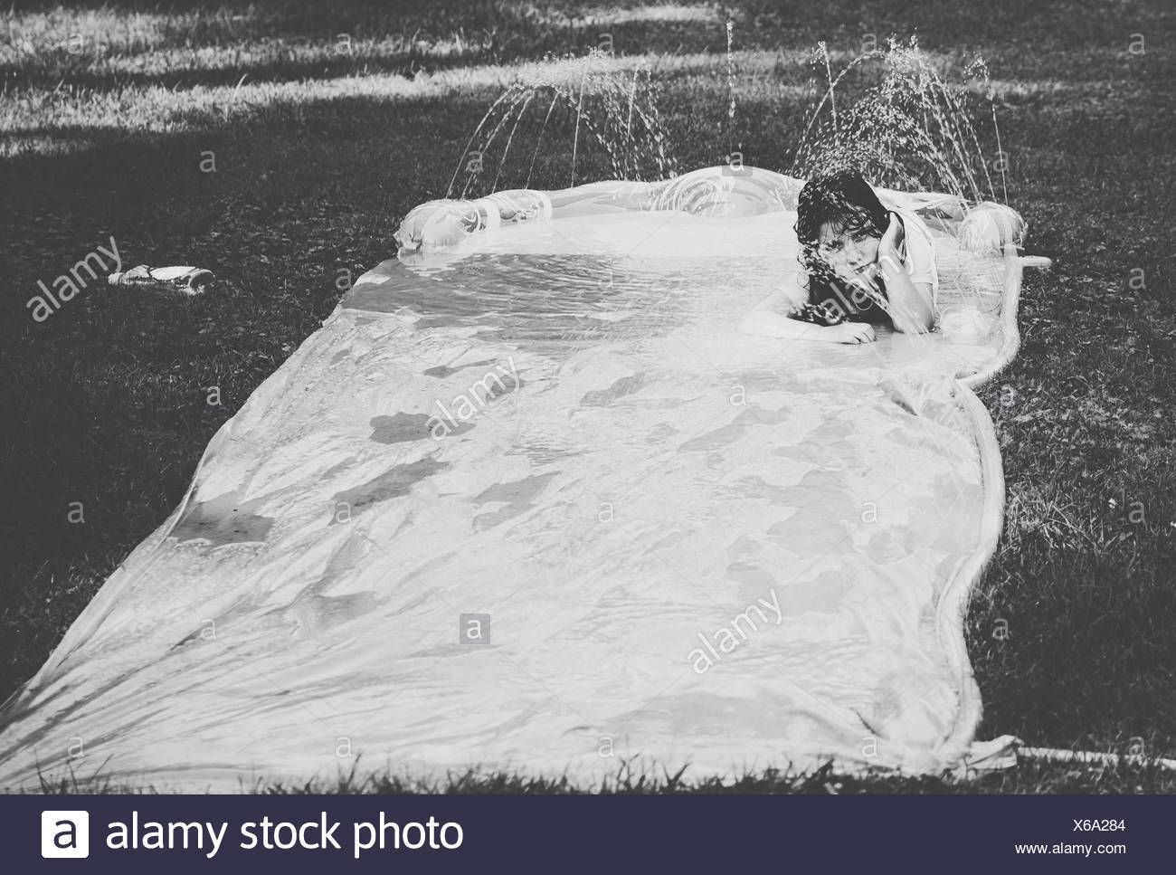 Portrait Of Girl Lying On Water Slide Canvas On Grass In Back Yard - Stock Image