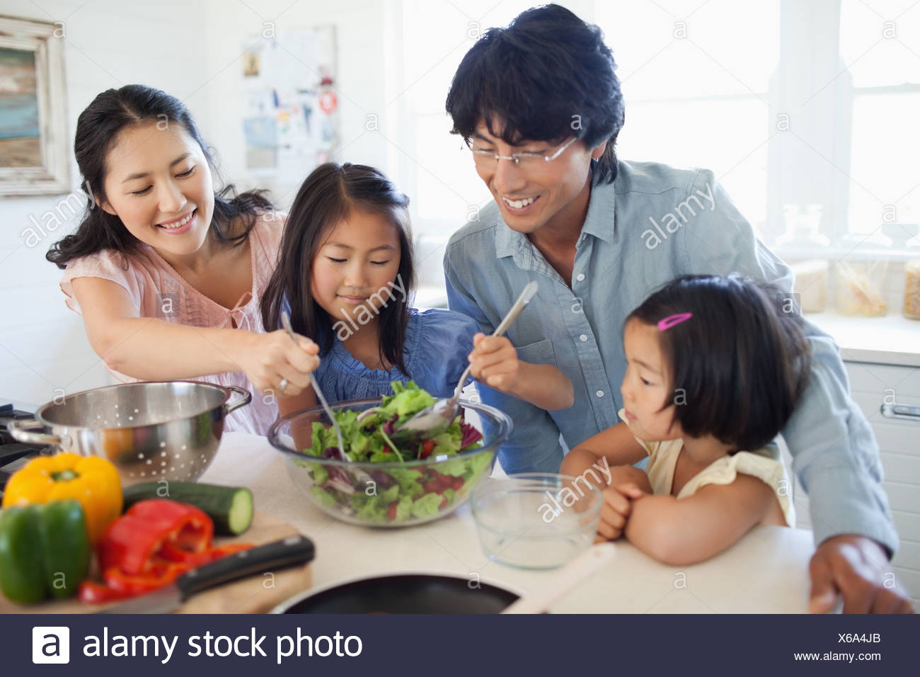 The mother and daughter toss the salad as the father and other daughter watch - Stock Image