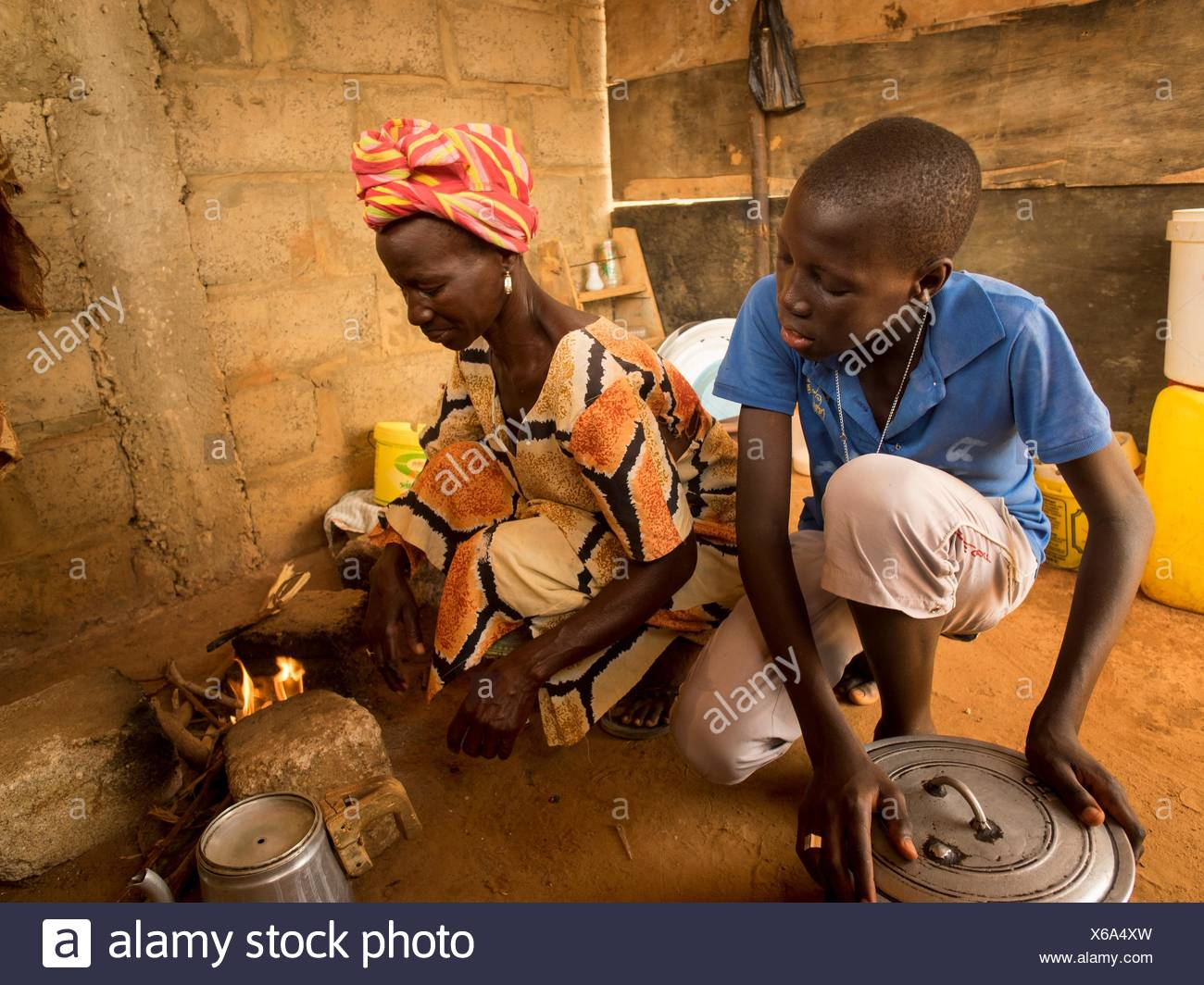 A boy helps his mother in their basic kitchen. - Stock Image