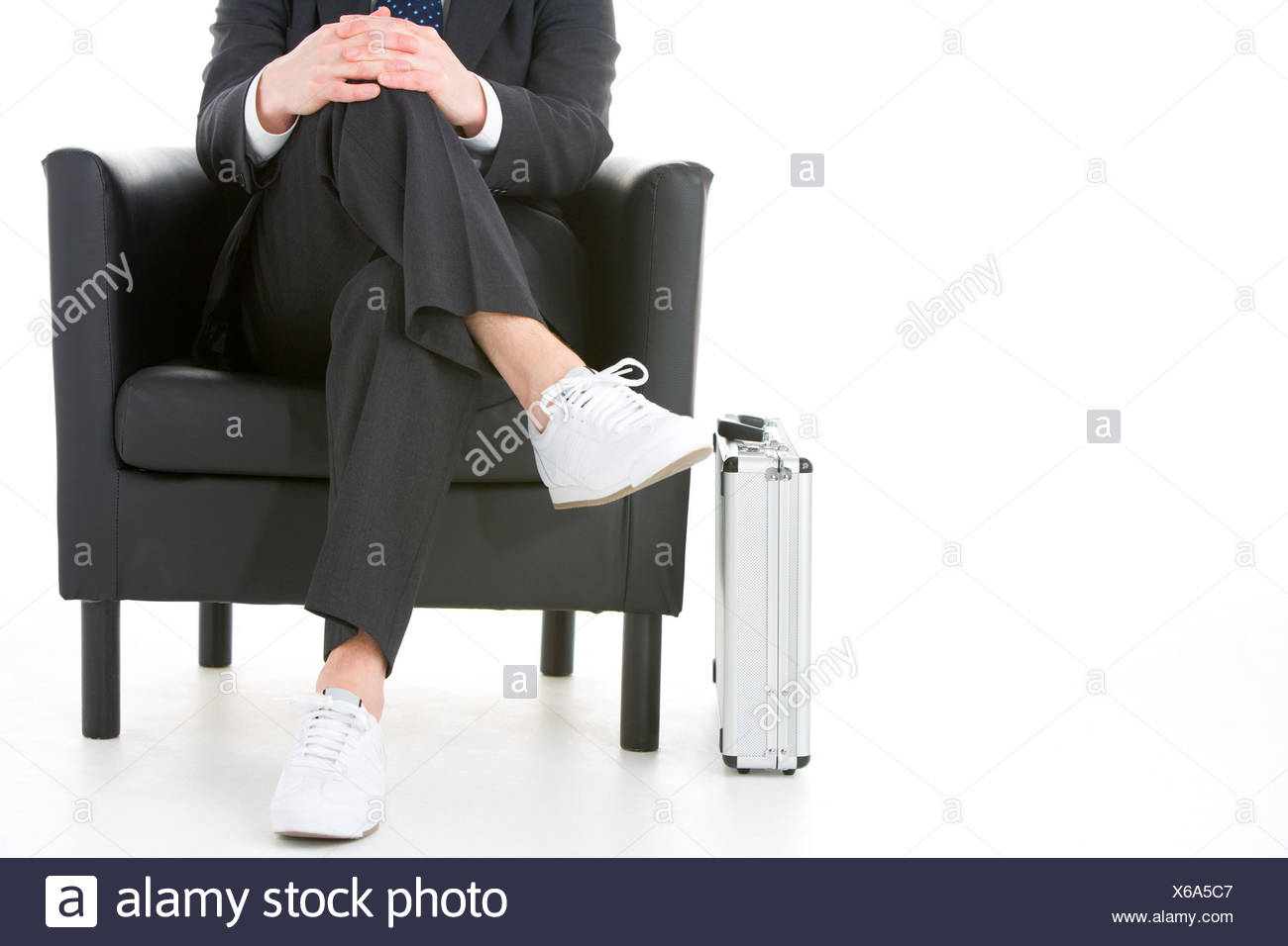 Businessman Sitting Wearing Sneakers - Stock Image