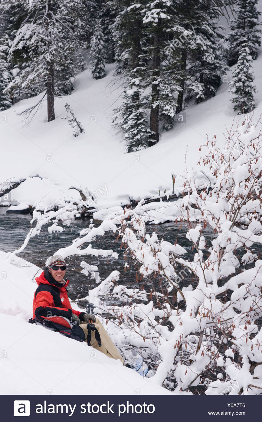 A man snow shoeing along the Truckee river while it snows in Truckee in California - Stock Image