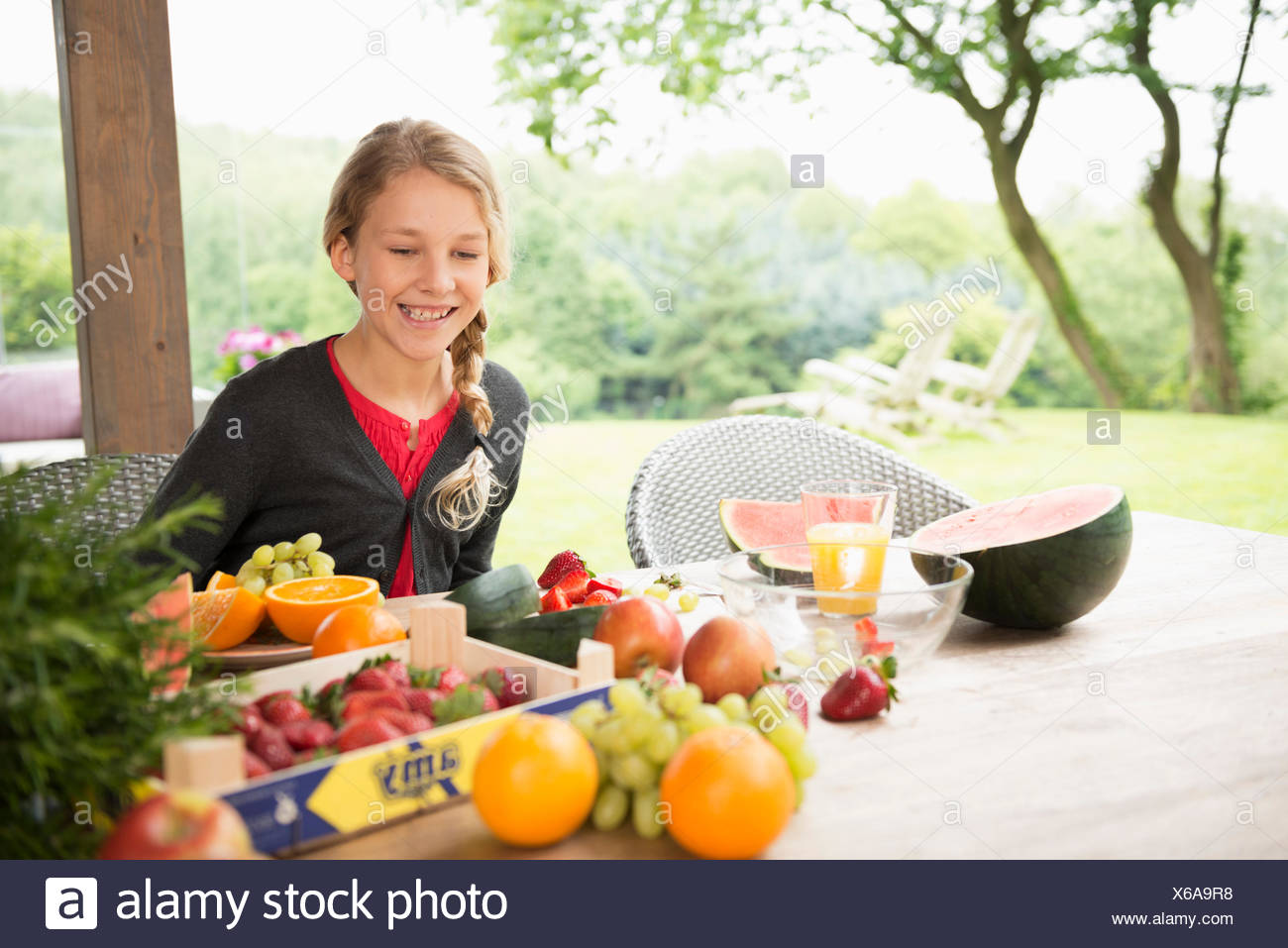 Girl at patio table with a variety of fresh fruit - Stock Image