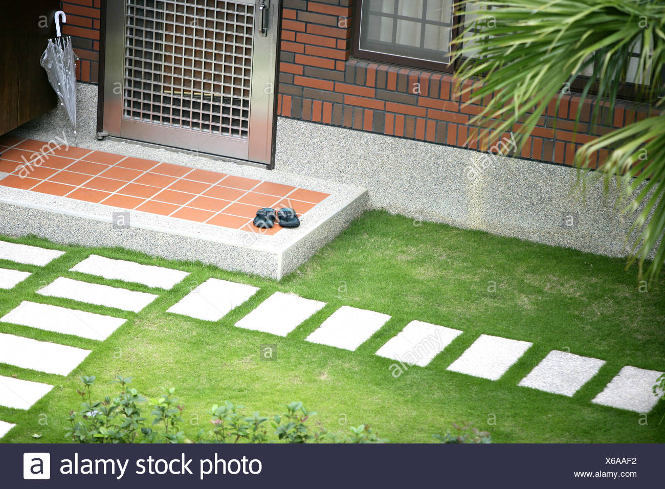 View Of Front Door With Grass And Stone Steps Stock Photo