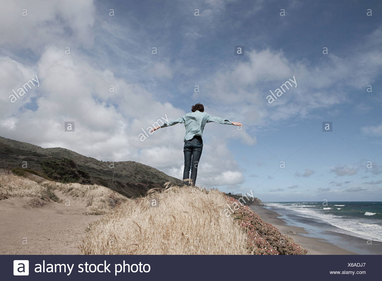 Young man standing on hill with arms out - Stock Image