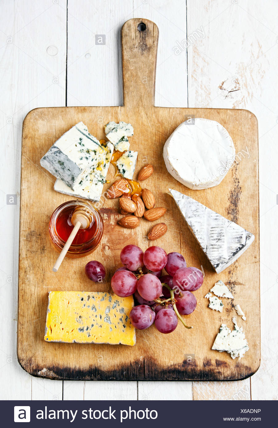 Assortment of various types of cheese on wooden board - Stock Image