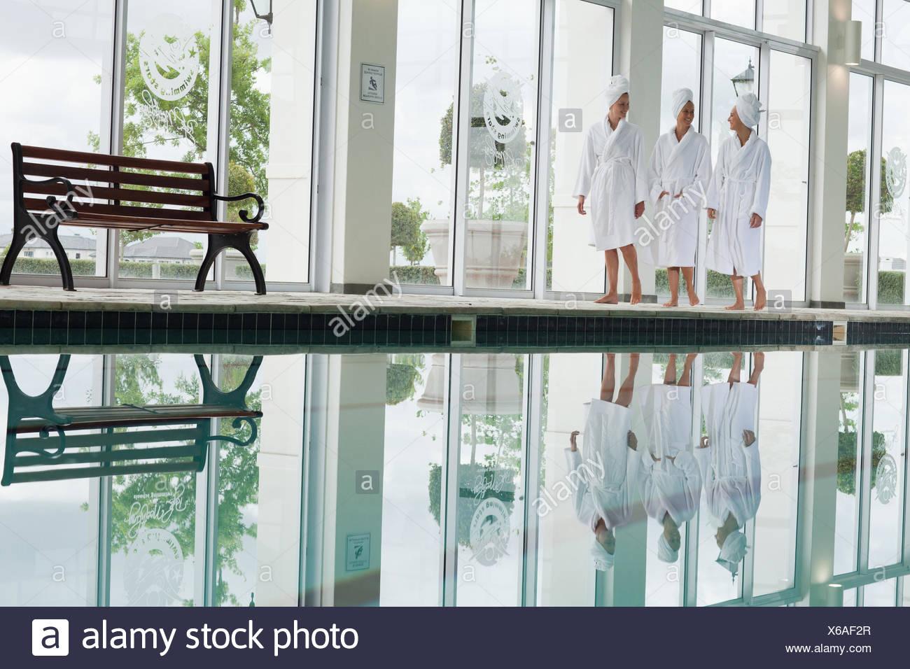 Women in bathrobes walking along swimming pool at spa Stock Photo