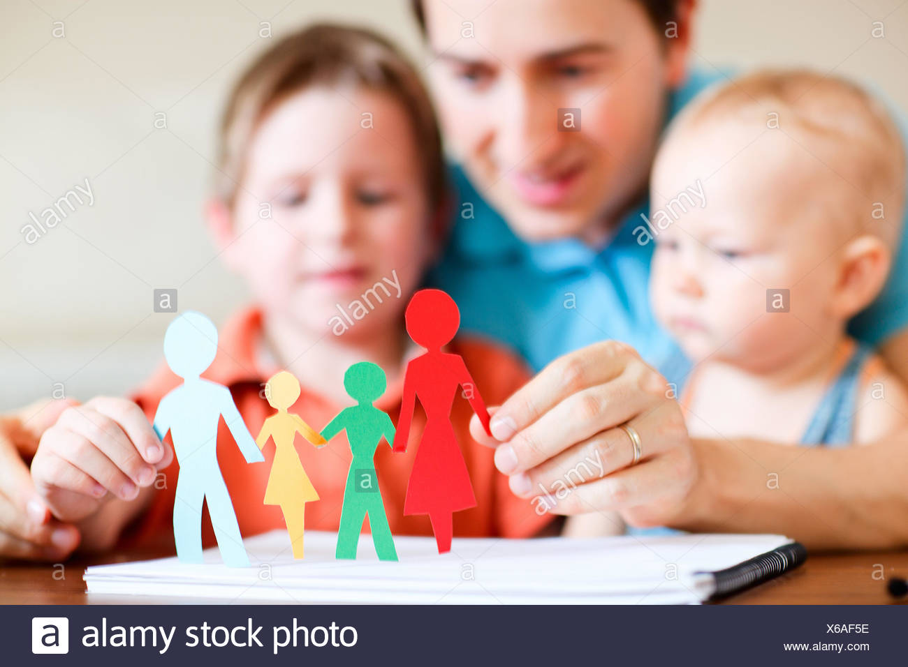 a father playing with his two children - Stock Image