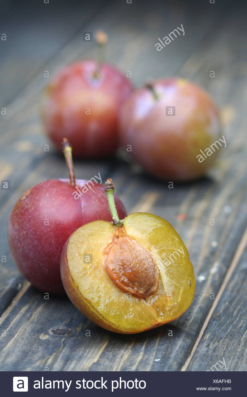 Plums on wooden table - close-up - Stock Image