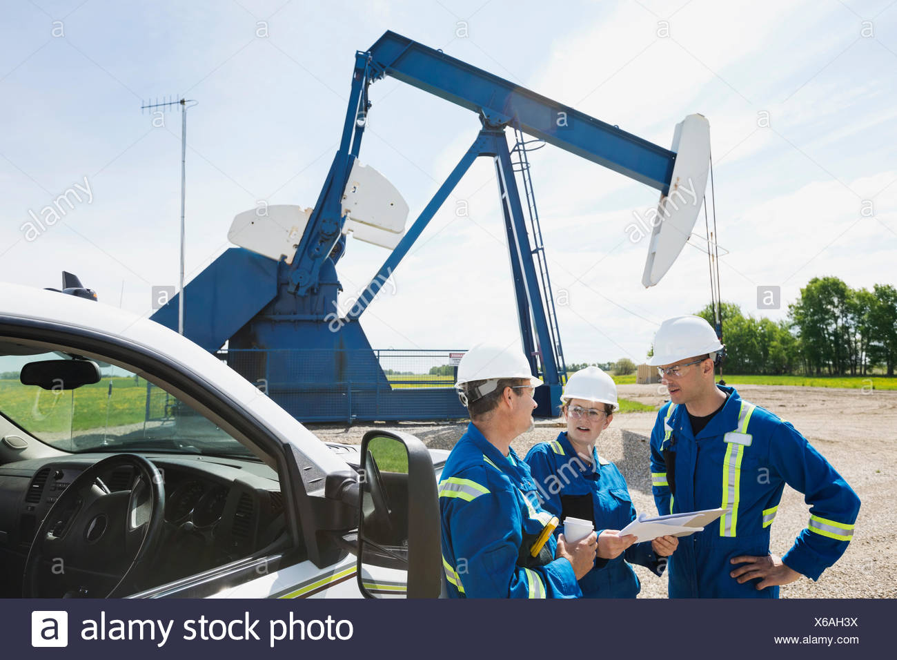Workers meeting near oil well - Stock Image