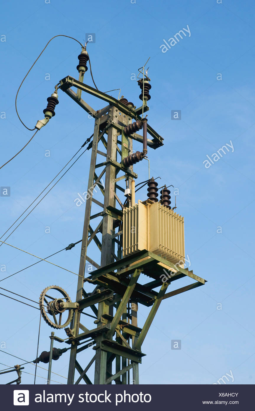 Power supply pylon with a transformer and insulators, with a tension sheave at the bottom to keep the lines taught - Stock Image