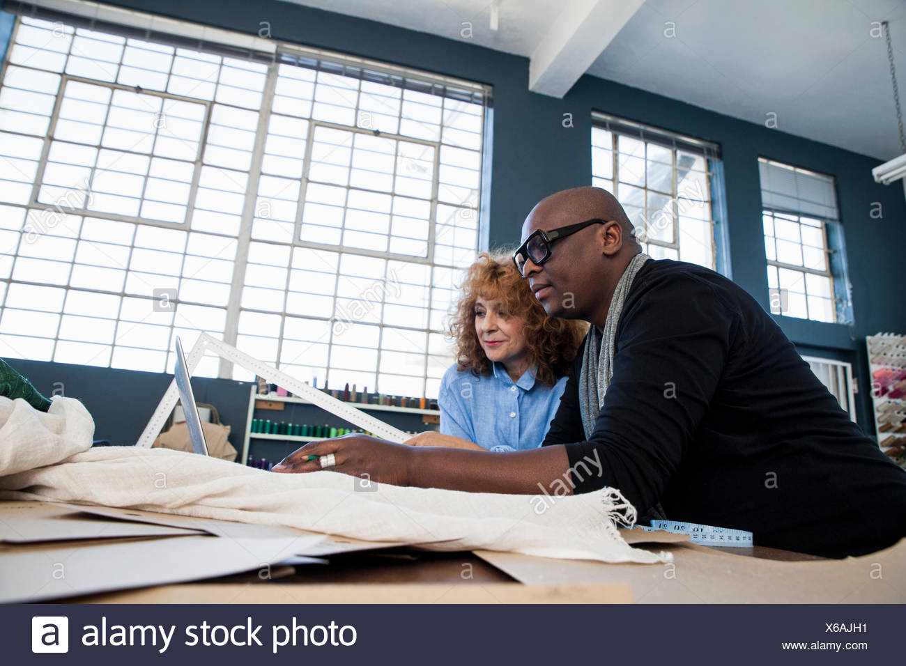 Female and male fashion design team looking at dressmaker's pattern in design studio - Stock Image