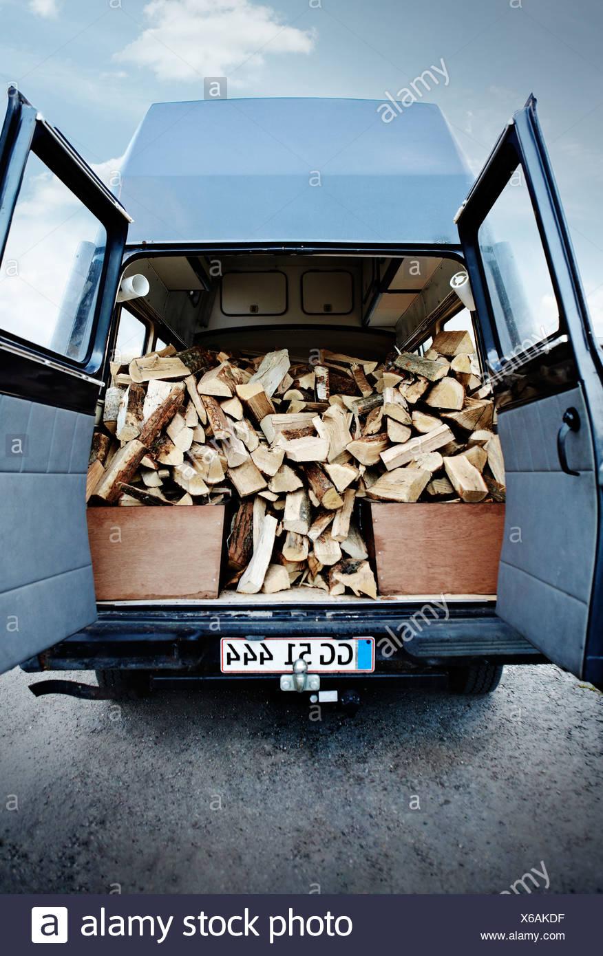 Firewood piled in van - Stock Image