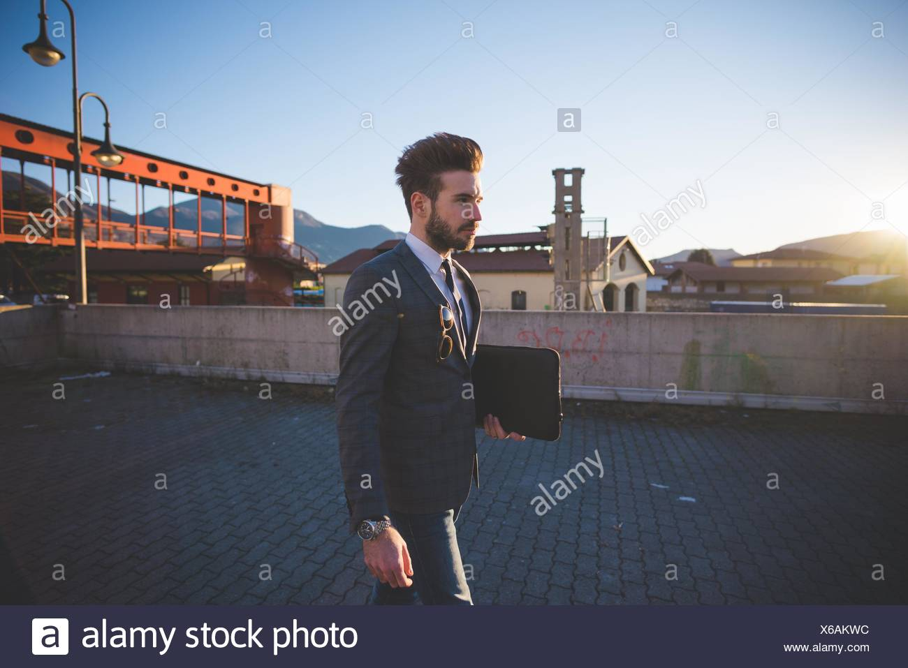 Young businessman carrying briefcase in urban area - Stock Image