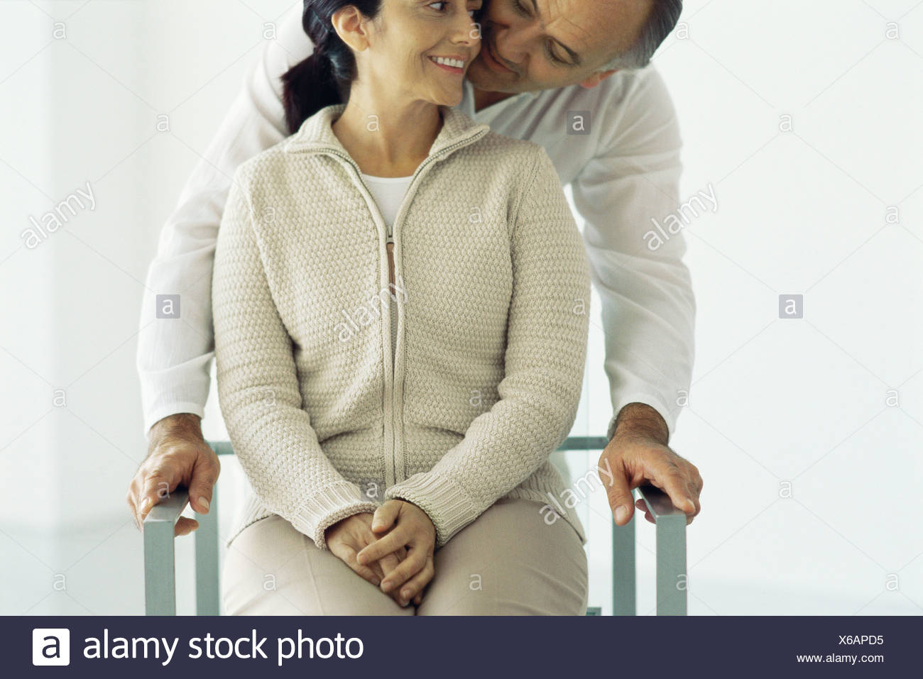 Woman sitting in chair, husband standing behind leaning down whispering in her ear, front view - Stock Image