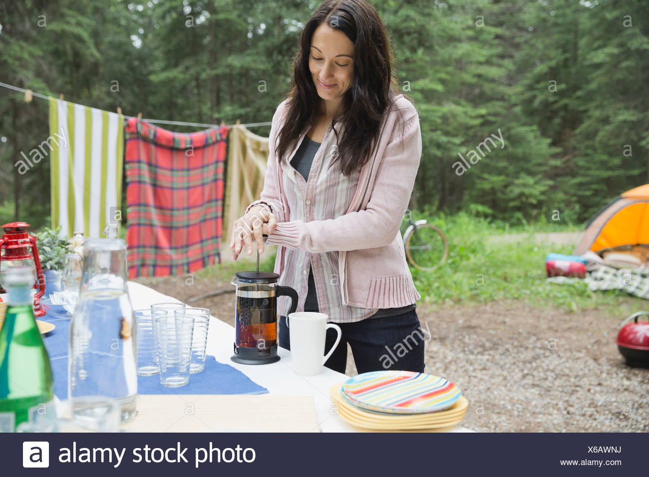 Woman using coffee press at campsite - Stock Image