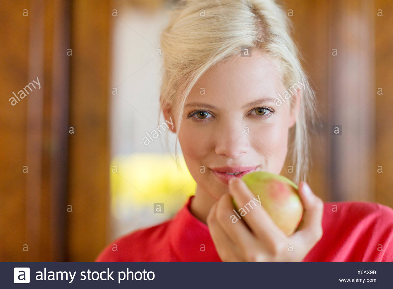 Woman eating apple indoors Stock Photo
