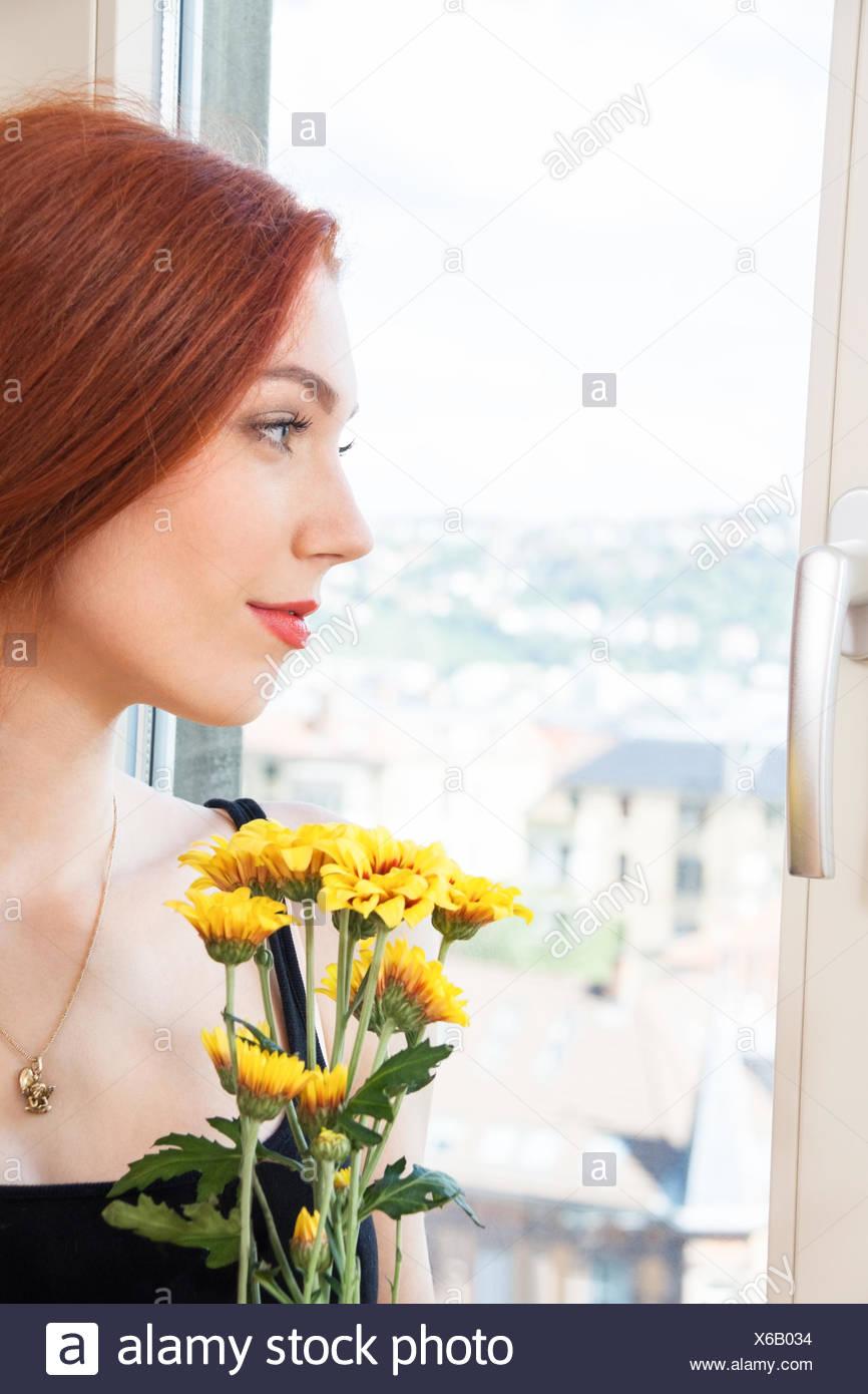 Thoughtful Woman with Flowers Leaning on Window - Stock Image