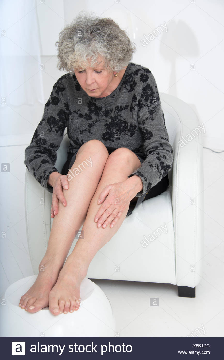 MODEL RELEASED. Senior woman sitting on a chair touching her legs. - Stock Image