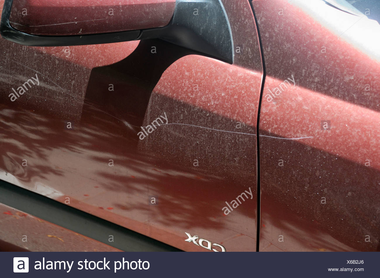 A vandalised car a long scratch along the side of the car - Stock Image