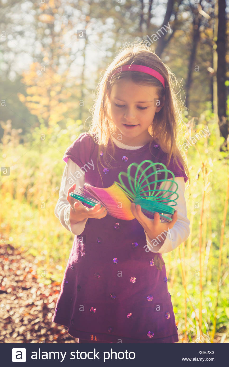 Little girl with spiral in prismatic colours - Stock Image