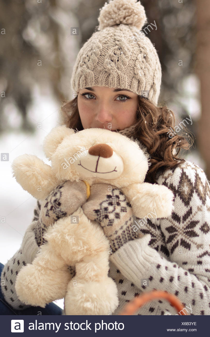 Beautiful, nice, smiling,little and wearing sweater hut and mittens and little girl with a teddy bear in winter forest.Portrait of lovely girl with cute,nice toy.Cute,beautiful,nice girl hug a fluffy,white,beige teddy bear.Girl and bear in winter Stock Photo