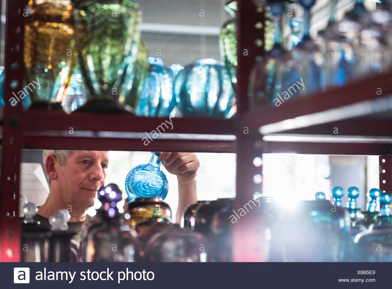 Glassblower inspecting finished glassware - Stock Image