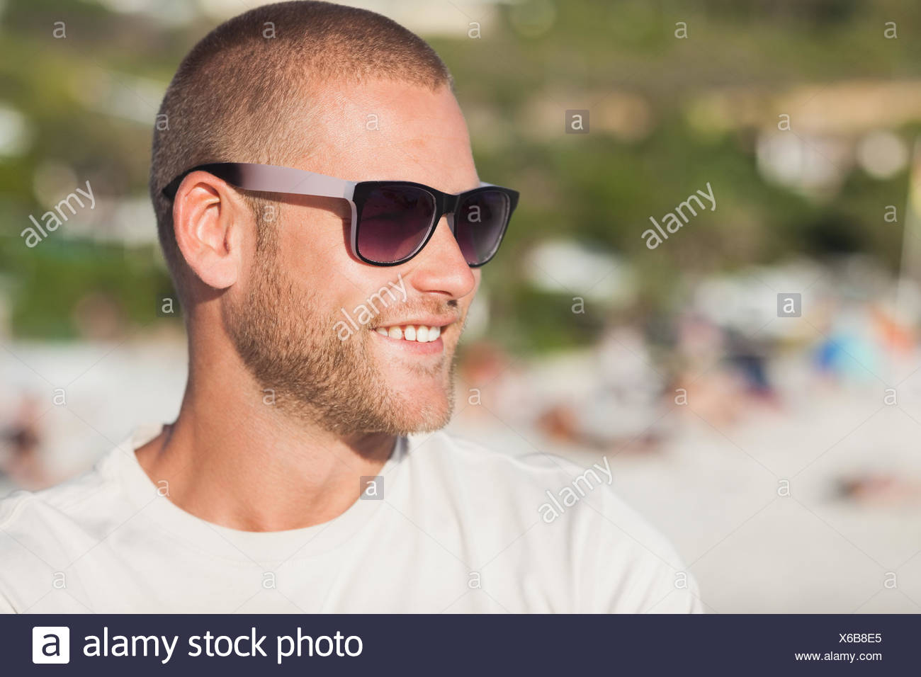 cdba2aa64763 Handsome young man on the beach wearing sunglasses looking away ...