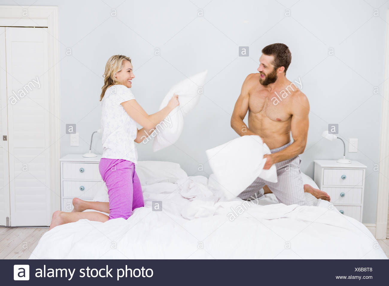Couple having a pillow fight in bed - Stock Image