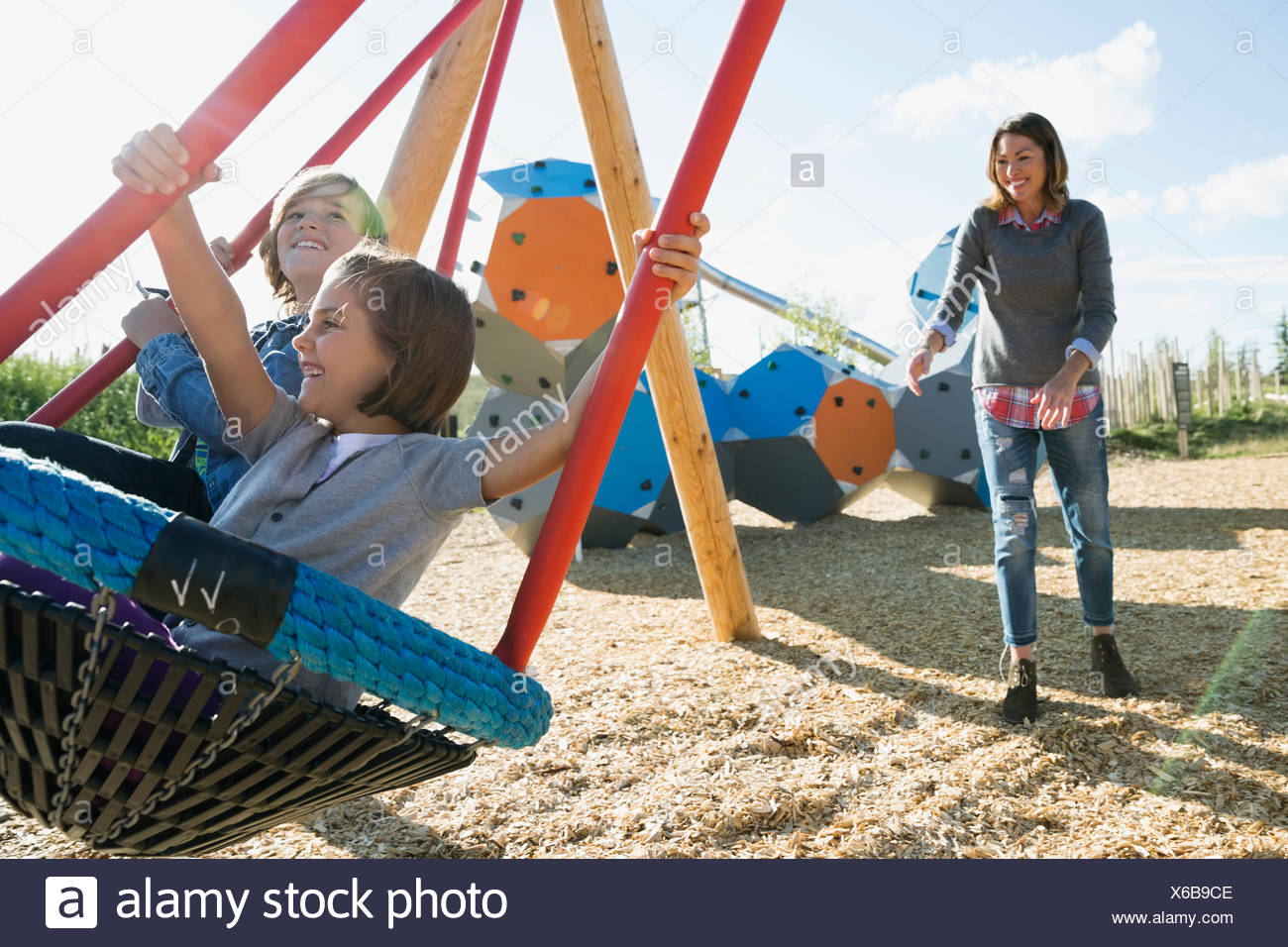 Mother pushing daughter and son in playground swing Stock Photo