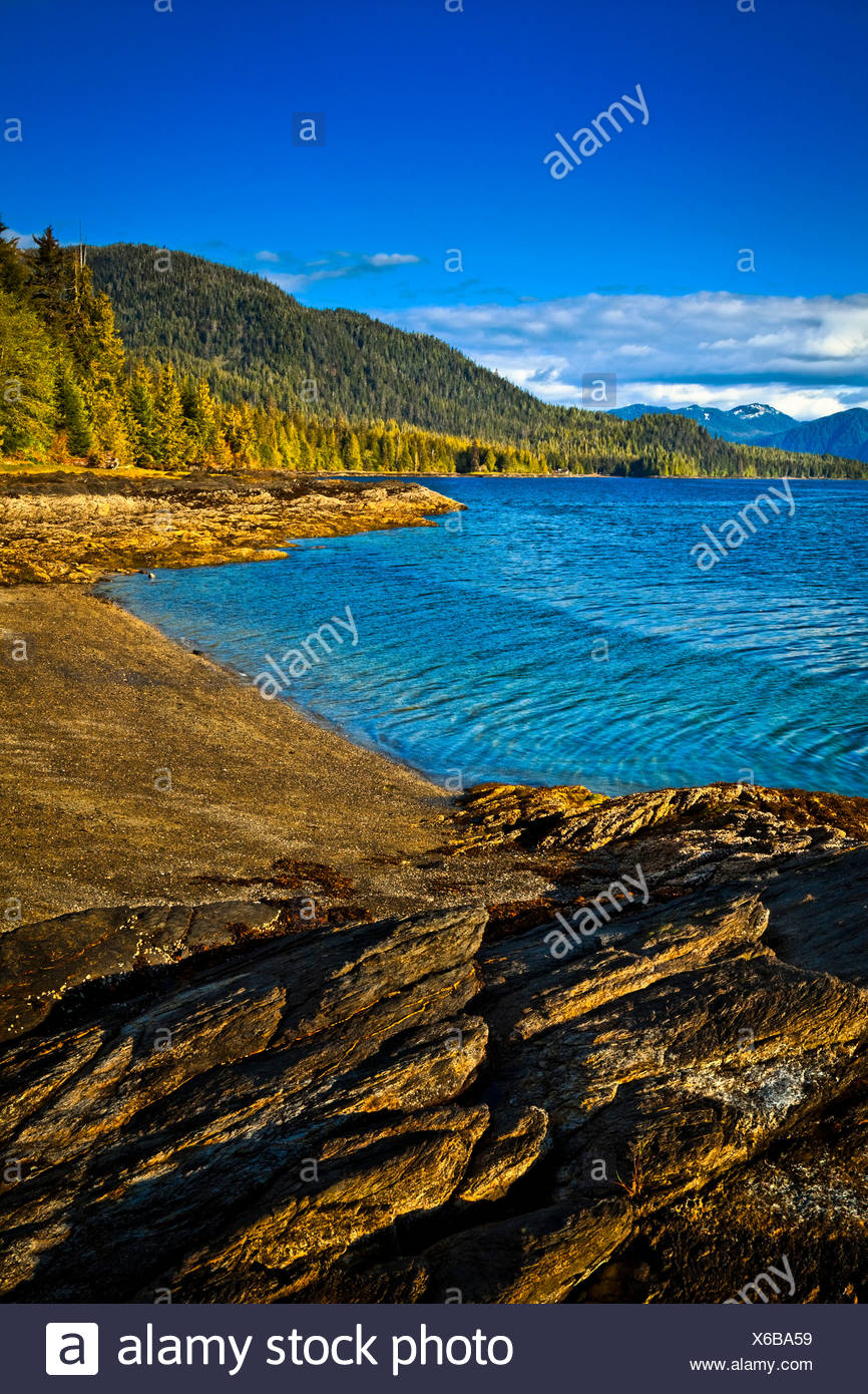 Sunlit rocks line the blue waters of Settler's Cove,  Settler's Cove State Recreation Site, Ketchikan, Southeast Alaska, Summer Stock Photo