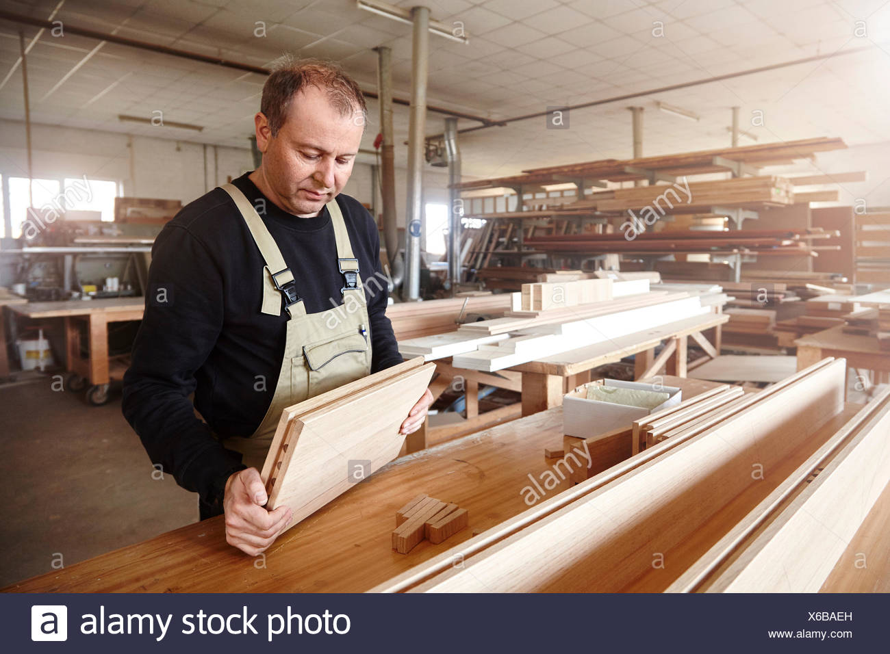 Male carpenter inspecting wood plank at workbench - Stock Image