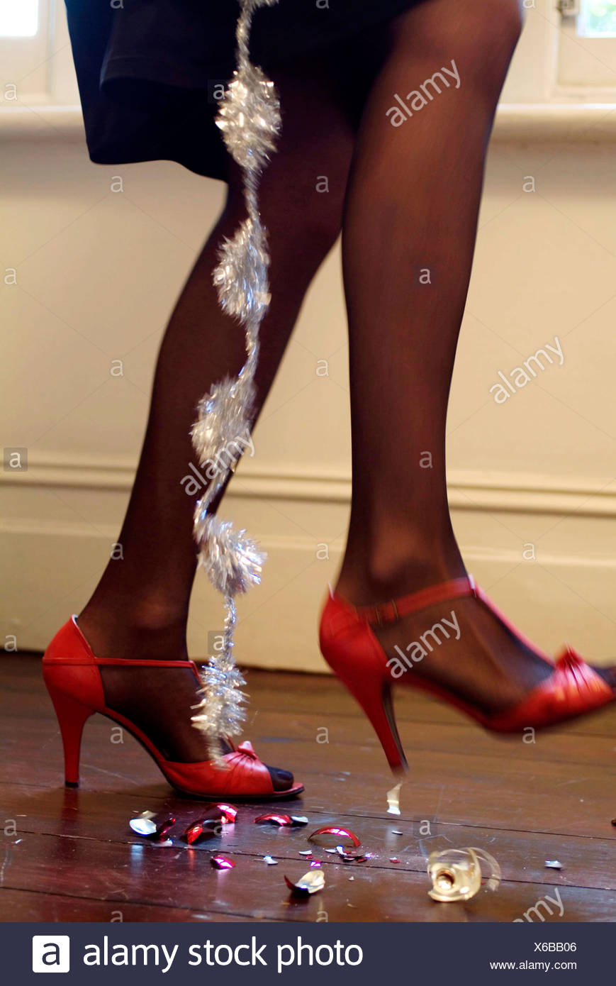 981f0648958e Cropped lower legs of female wearing black tights and red high heeled shoes  strap at ankle