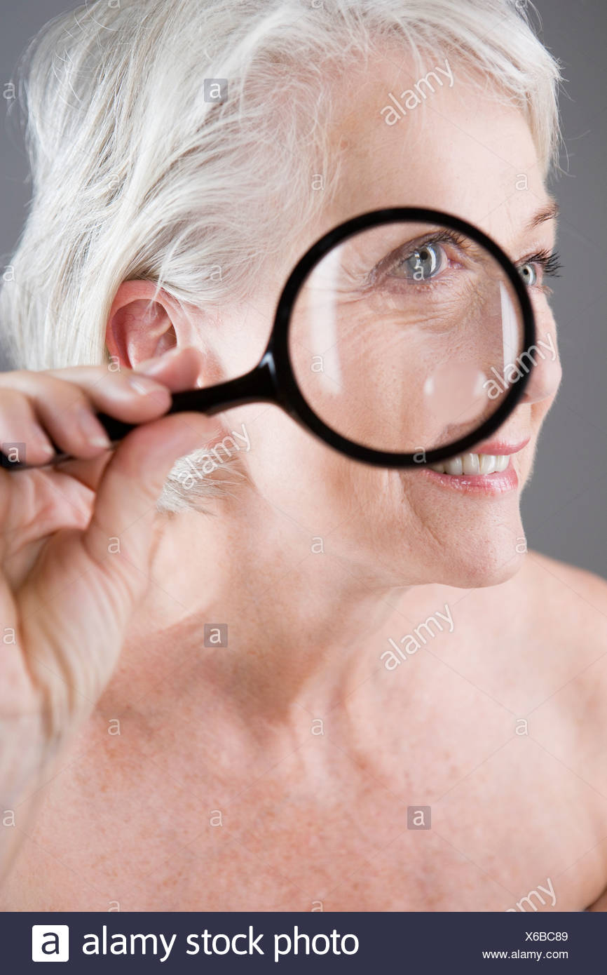 A senior woman using a magnifying glass - Stock Image