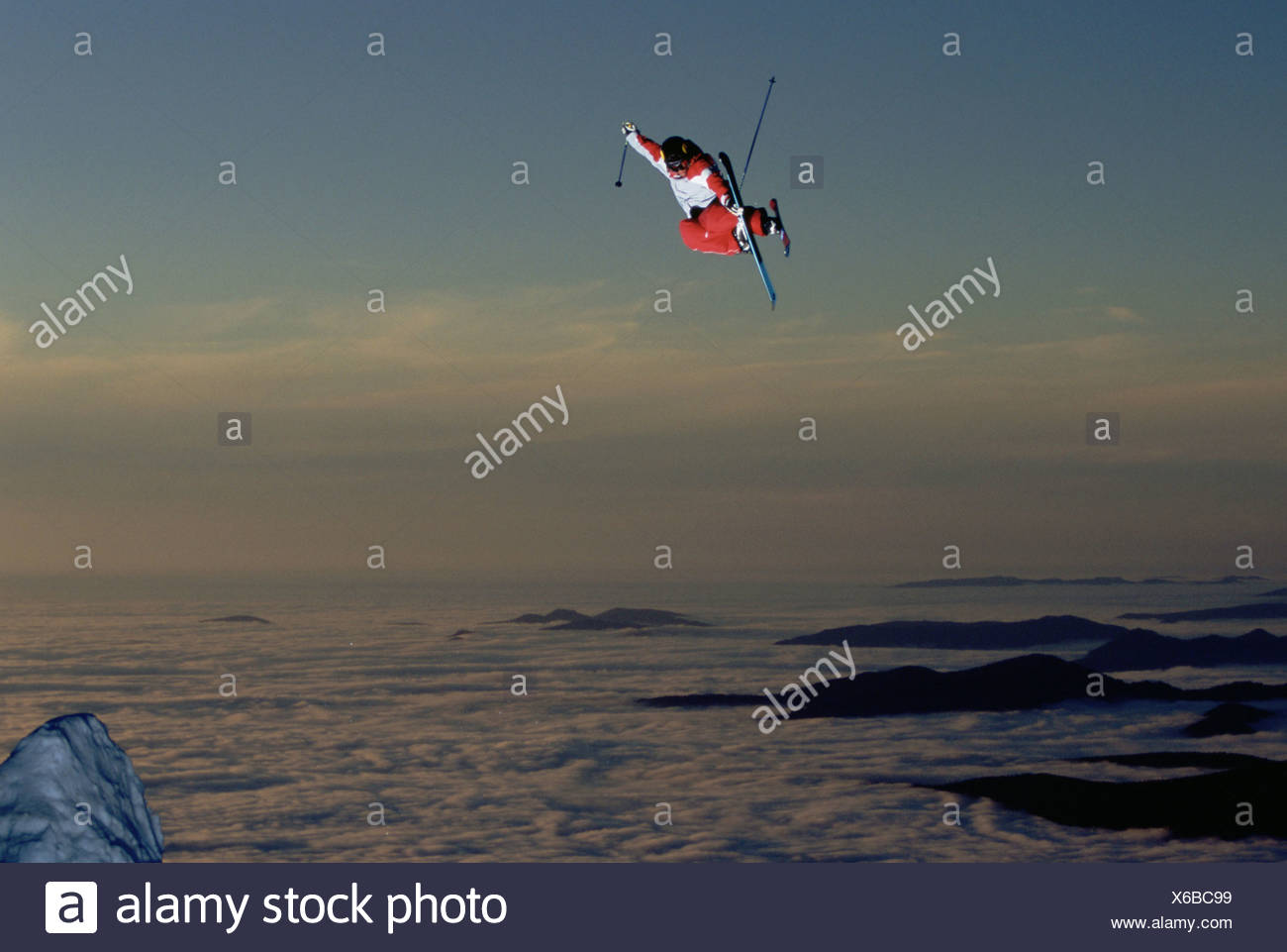 A skier jumps high into the air. - Stock Image