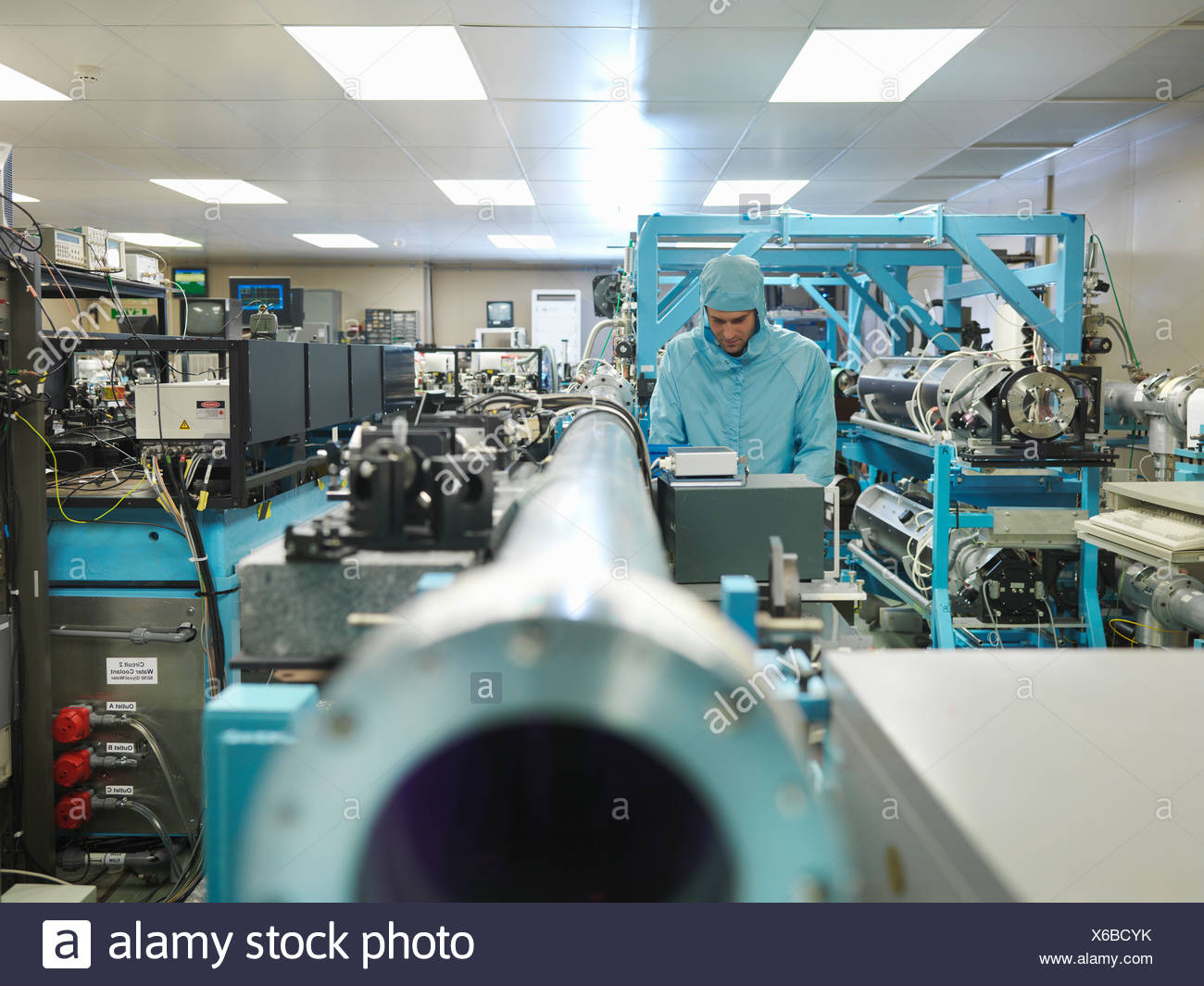Scientist in laboratory with laser - Stock Image