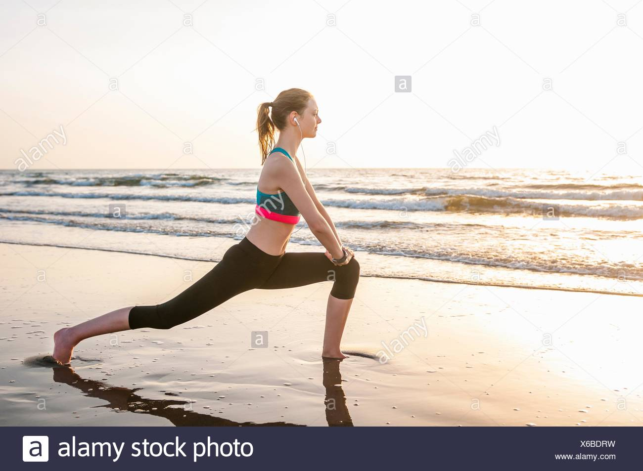 Side view of mid adult woman by ocean doing lunge, hands on knees Stock Photo