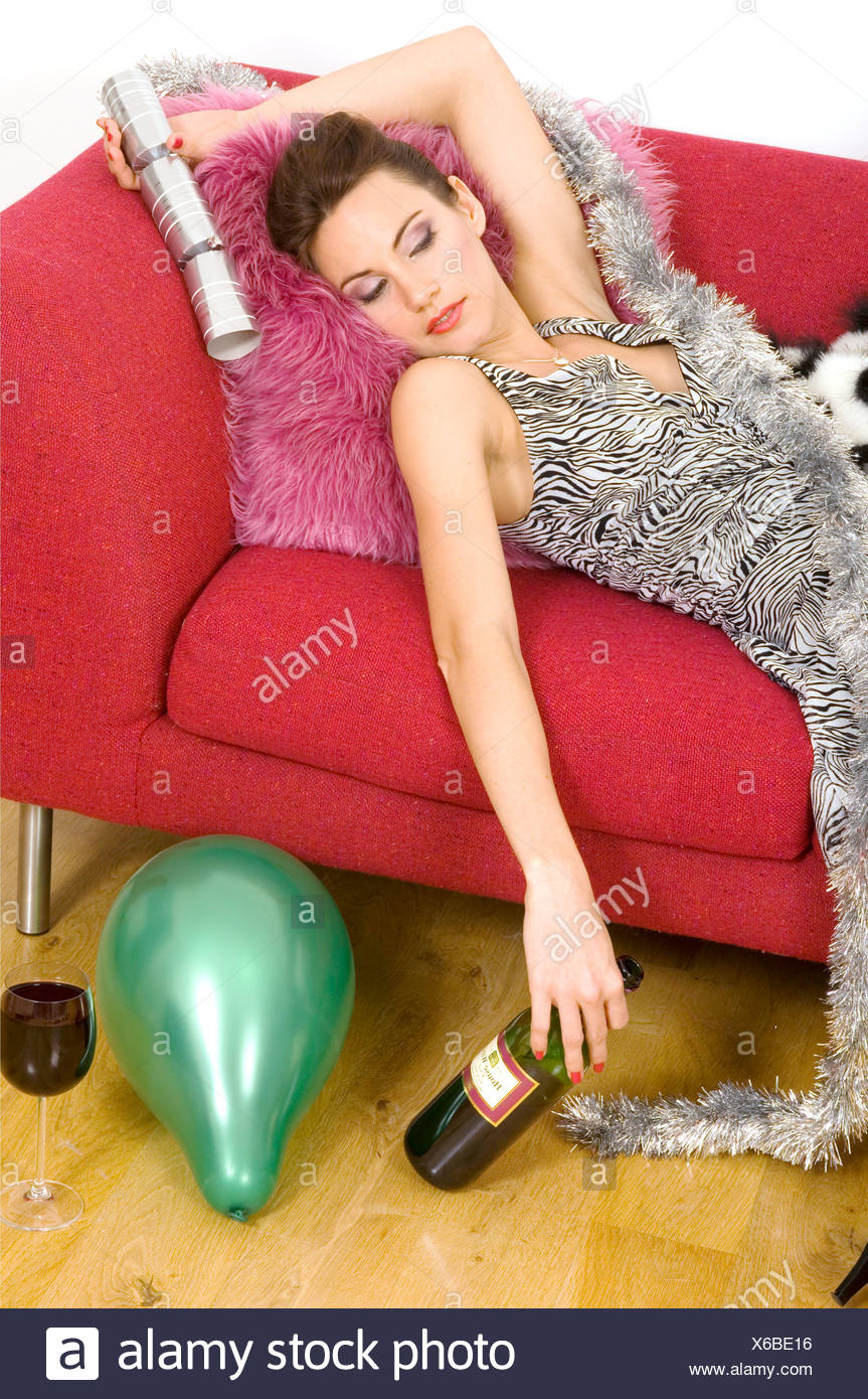 Brunette female hair in a chignon, wearing a black and white patterned  dress passed out on a sofa holding a Christmas cracker