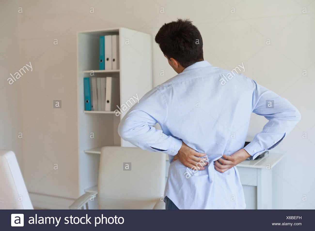 Casual businessman touching his sore back - Stock Image