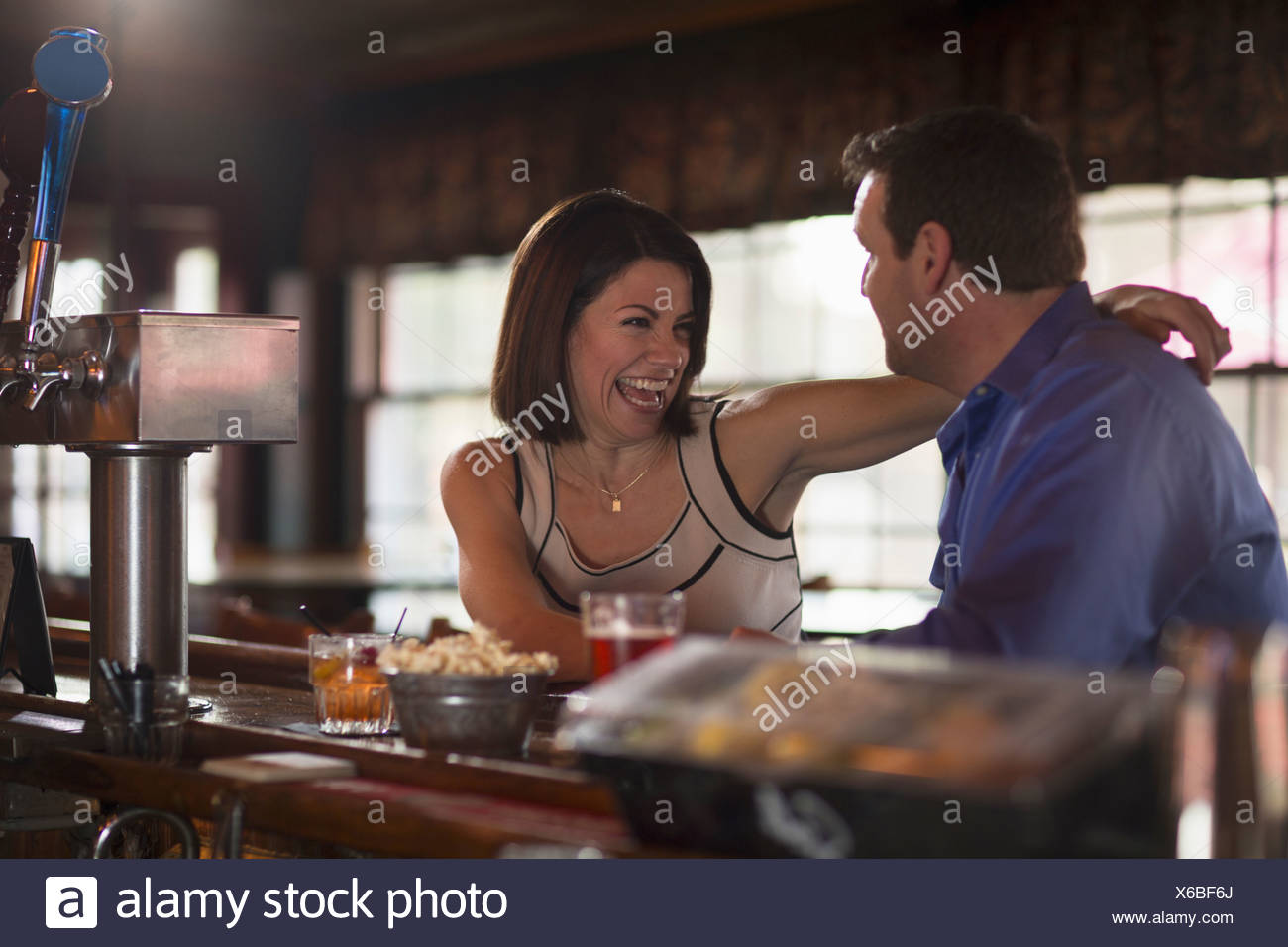 A man and woman seated at a bar flirting and talking On a date New Hope Pennsylvania USA - Stock Image